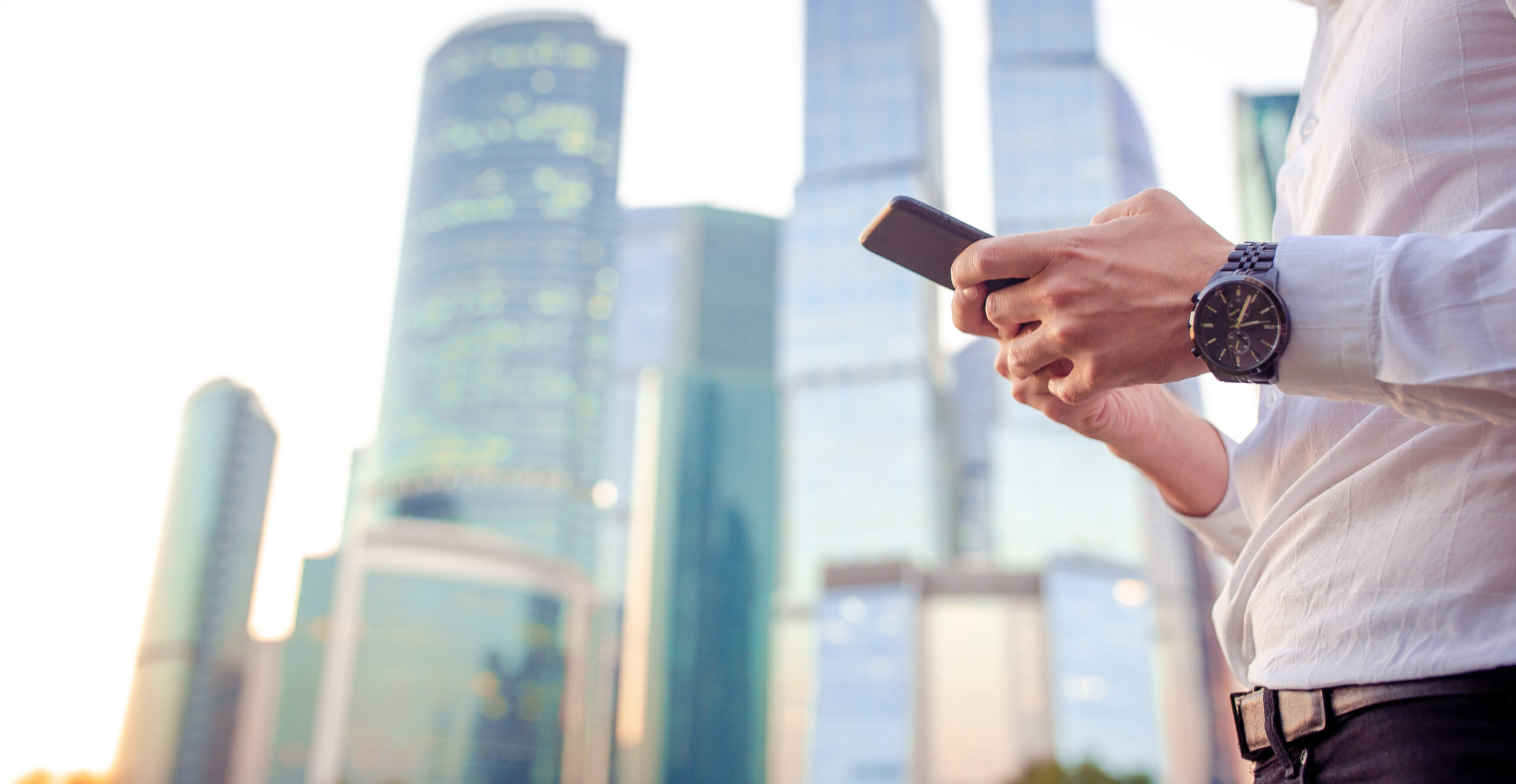 Closeup of male hands is holding cellphone with skyscrapers buildings in the background. Closely of businessman search information in network with smart phone